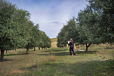 Artist with easel sketching in olive tree grove - p1125m2073231 by jonlove