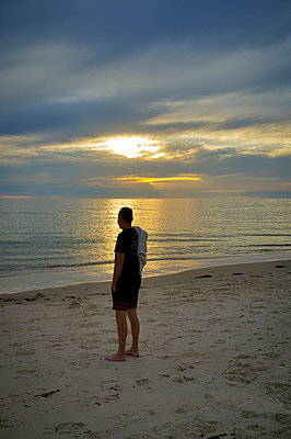Adult man standing on beach contemplating sunset at seashore  - p1125m2073241 by jonlove