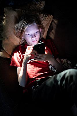 Top down of boy scrolling on smart phone - p1166m2131130 by Cavan Images