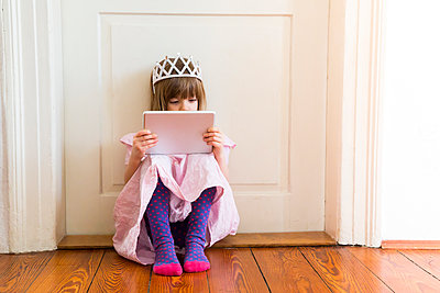 Little girl dressed up as a princess looking at digital tablet - p300m1188722 by Larissa Veronesi