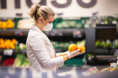 Teenage girl wearing protectice mask and gloves choosing fruits at supermarket - p300m2225035 by Anke Scheibe