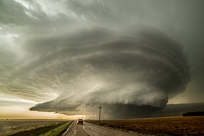 Storm chaser driving towards an supercell that has already produced three tornadoes and  is about to produce a fourth, Leoti, Kansas, USA - p429m1494496 by Jessica Moore