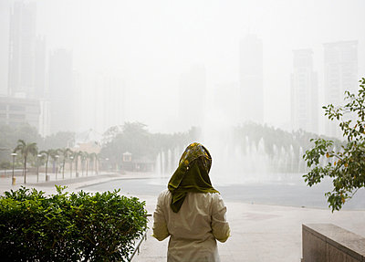Young muslim woman waiting for rain to end - p9241742 by Samantha Mitchell