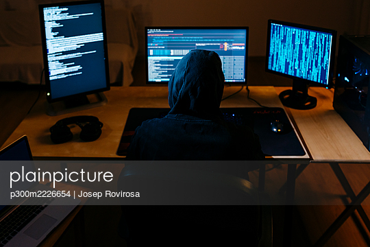 Computer hacker doing coding on computer while sitting at office - p300m2226654 by Josep Rovirosa
