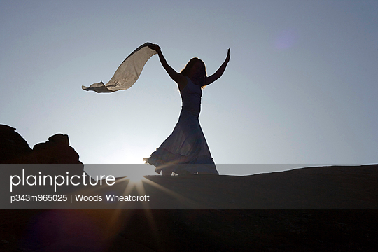 Woman in long dress holds up a scarf in desert. - p343m965025 by Woods Wheatcroft photography
