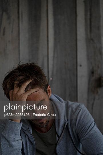 Sad man sitting in stilt hut - p623m2258126 by Frederic Cirou