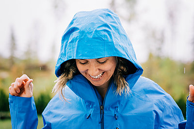 woman stood in the rain smiling outside in a raincoat - p1166m2193805 by Cavan Images