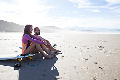 Smiling couple with surfboards sitting on the beach - p300m1204744 by Andrés Benitez