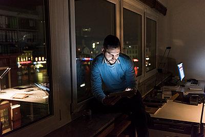 Businessman sitting on window sill in office at night using tablet - p300m1581406 von Uwe Umstätter