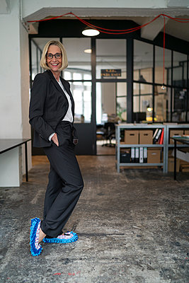 Portrait of smiling mature businesswoman wearing cleansing slippers in office - p300m2156097 by Gustafsson