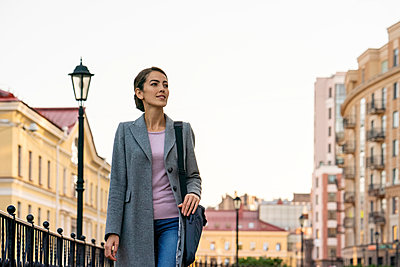 Female entrepreneur looking away while walking in city during autumn - p300m2241376 by Vasily Pindyurin