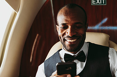Smiling businessman text messaging on smart phone in private jet - p300m2257071 by OneInchPunch