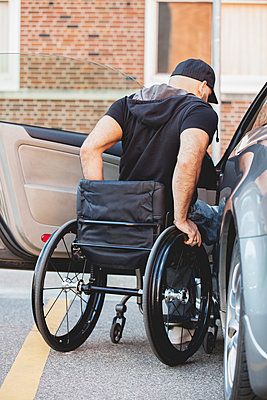 Disabled man in wheelchair climbing into car - p555m1410900 by PhotoAbility