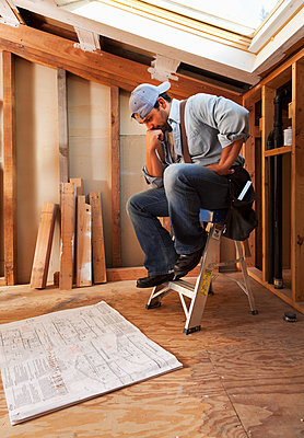 Hispanic construction worker looking at blueprints - p555m1478410 by Tanya Constantine