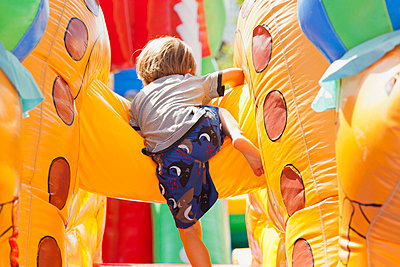 Boy playing in bouncy castle, rear view - p623m664242f by Frederic Cirou