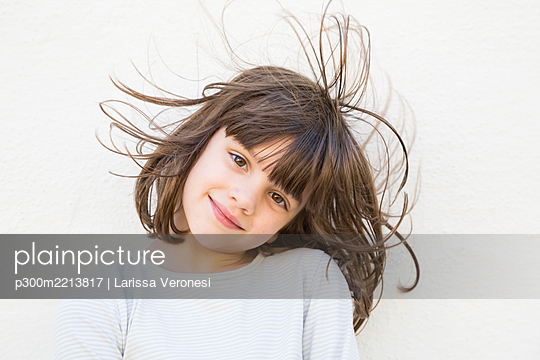 Portrait of smiling little girl with wafting hair - p300m2213817 by Larissa Veronesi
