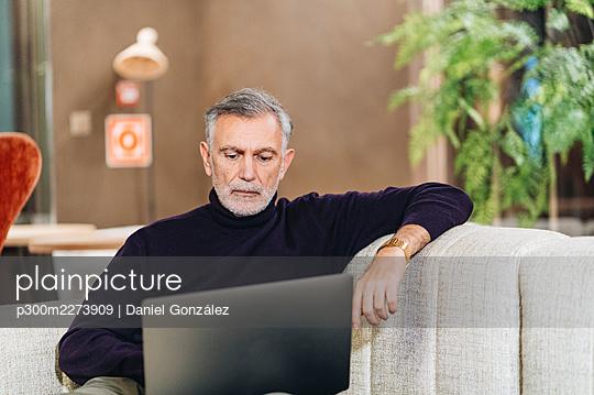 Mature businessman working on laptop at hotel - p300m2273909 by Daniel González