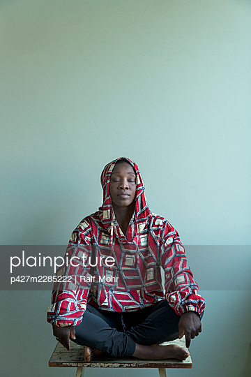 African woman sitting on a stool - p427m2285222 by Ralf Mohr
