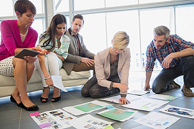 Creative business people reviewing proofs in office - p1192m1023946f by Hero Images