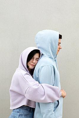 Girlfriend embracing boyfriend by wall - p300m2276298 by Petra Stockhausen