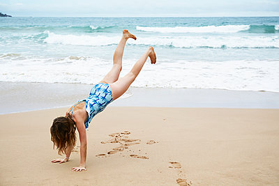 Girl doing handstand on beach - p312m1570815 by Anna Kern