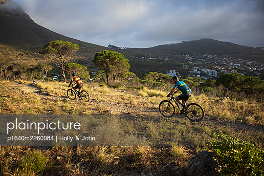 Two mountain bikers at sunset - p1640m2260984 by Holly & John
