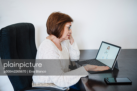 Senior woman gesturing while talking with doctor through video call on laptop at home - p300m2265670 by Eva Blanco