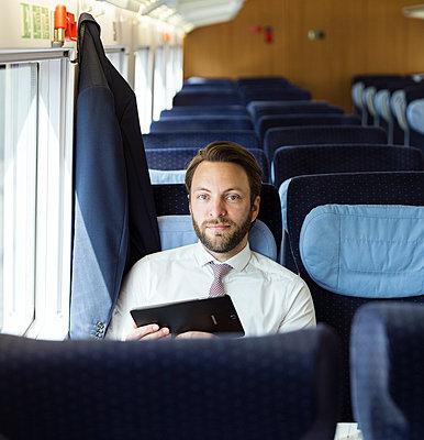 Geschäftsmann mit Tablet im Zug - p1114m1159776 von Carina Wendland