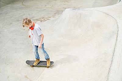 Boy with headphones on skateboard, skateboarding - p300m1586958 von Philipp Dimitri