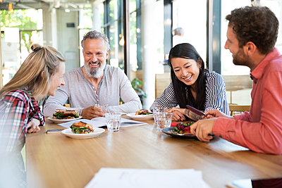 Happy casual business people having business lunch in a cafe - p300m2139864 by Florian Küttler