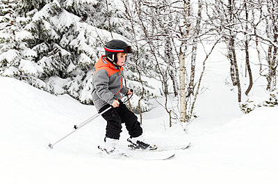 Boy skiing - p312m1558053 by Peter Rutherhagen