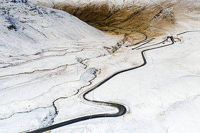 Aerial view by drone of S-shape road towards Stelvio Pass in the snowy landscape, Bormio, Sondrio province, Valtellina, Lombardy, Italy, Europe - p871m2152456 by Roberto Moiola