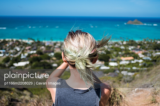 girl staring at the ocean on a pill box bunker in hawaii - p1166m2208029 by Cavan Images