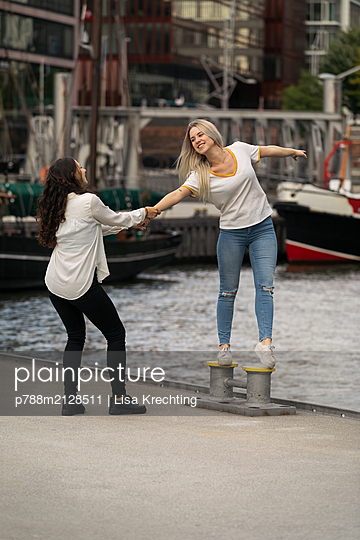 Two girlfriends have fun on the waterfront - p788m2128511 by Lisa Krechting