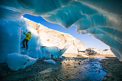 Man ice climbing on glacial ice during adventure helicopter tour - p1166m2159597 by Cavan Images