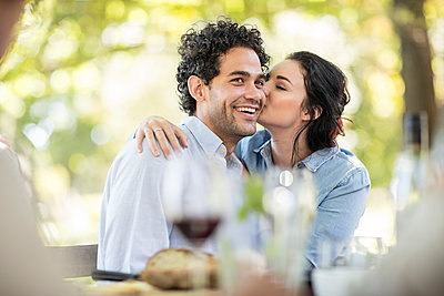 Young woman kissing a happy young man at outdoor table - p300m1204919 by zerocreatives