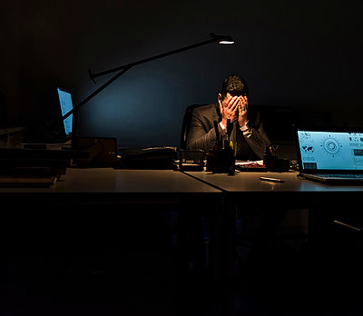 Overstressed businessman sitting at his desk in the dark - p300m1581243 von Uwe Umstätter