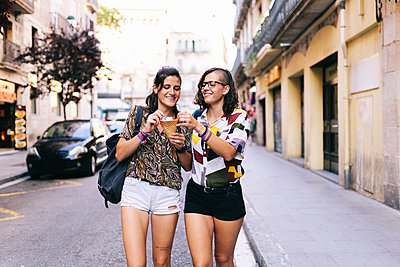 Homosexual couple holding ice cream walking on street in city - p300m2225117 by Daniel González