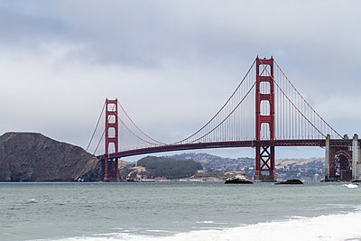 Golden Gate Bridge over bay of water against sky during foggy weather, San Francisco,  - p301m1180721 by Britta Wendland