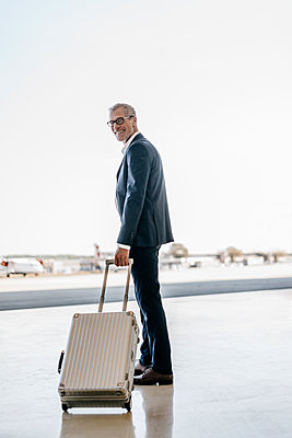 Businessman with trolley suitcase on airfield - p586m1208568 by Kniel Synnatzschke