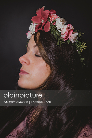 Dark haired woman with floral wreath in her hair - p1628m2244853 by Lorraine Fitch