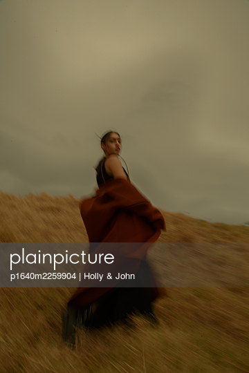Young woman in brown coat - p1640m2259904 by Holly & John