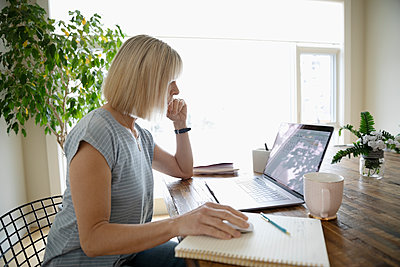 Woman working from home, using laptop at dining table - p1192m2088346 by Hero Images