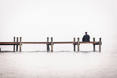 Back view of man sitting on jetty at Lake Starnberg, Germany - p300m2140747 von Wilfried Feder