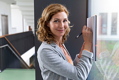Portrait of smiling businesswoman taking notes at windowpane in office - p300m2155521 by Buero Monaco