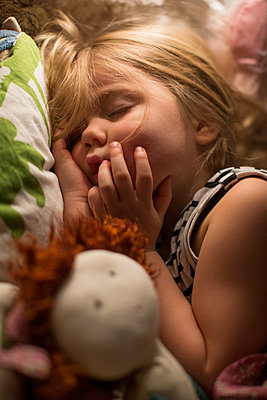 Small girl sleeping in bed - p312m1229019 by Peter Rutherhagen