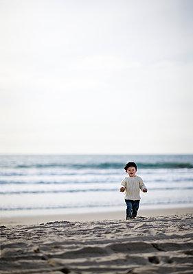 USA, California, Los Angeles, Santa Monica, Boy (2-3) walking on beach - p352m1100099f by Fredrik Ottosson