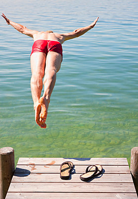 Man in swimsuit jumping into lake - p42916674f by Henglein and Steets
