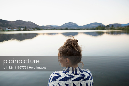 Serene young woman in sweater at lake at dusk - p1192m1183776 by Hero Images