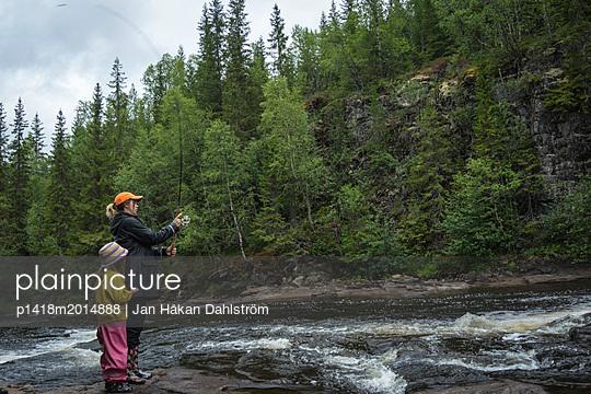 Junge Frau beim Angeln mit ihrer Tochter - p1418m2014888 von Jan Håkan Dahlström